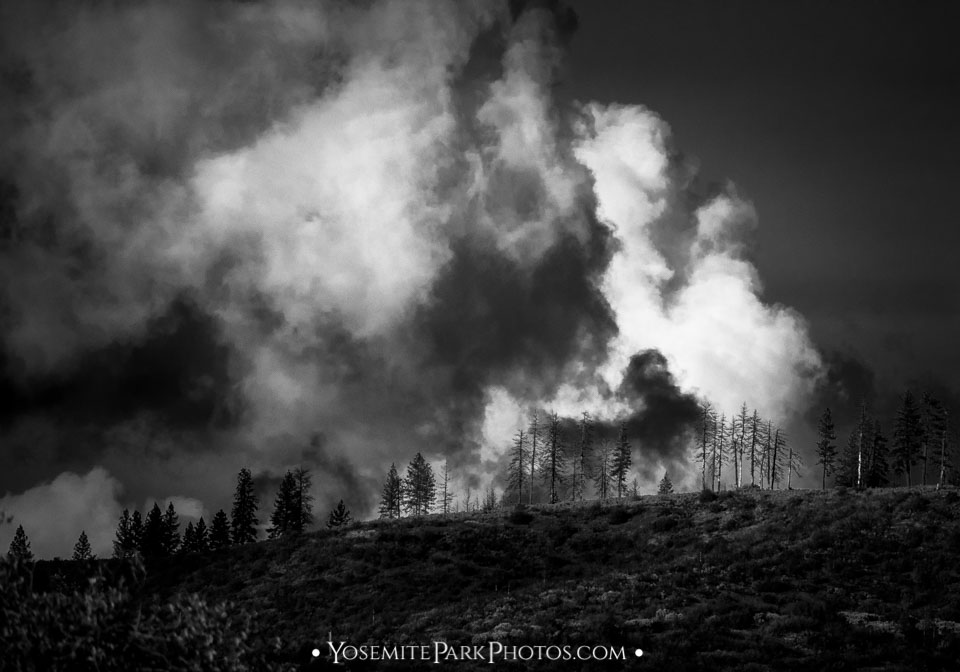 Smoke-like cumulus cloud formation illuminated on hilltop - black and white